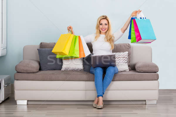Woman Holding Shopping Bag With Laptop On Couch Stock photo © AndreyPopov