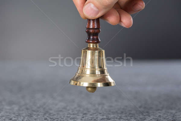 Person Hand Holding A Ring Bell Stock photo © AndreyPopov