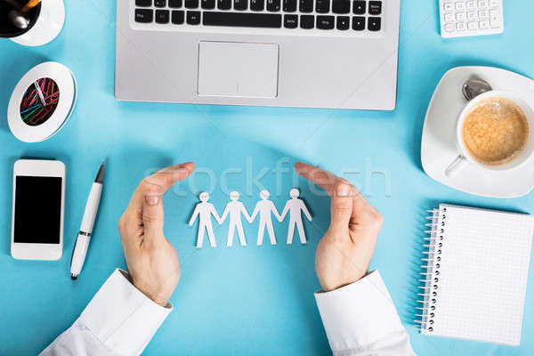 Businessman Protecting The Paper Cut Out Human Figure Stock photo © AndreyPopov
