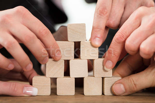 People Arranging Block On Pyramid Stock photo © AndreyPopov