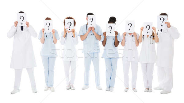 Group Of Multiracial Doctors Hiding Behind Question Mark Sign Stock photo © AndreyPopov