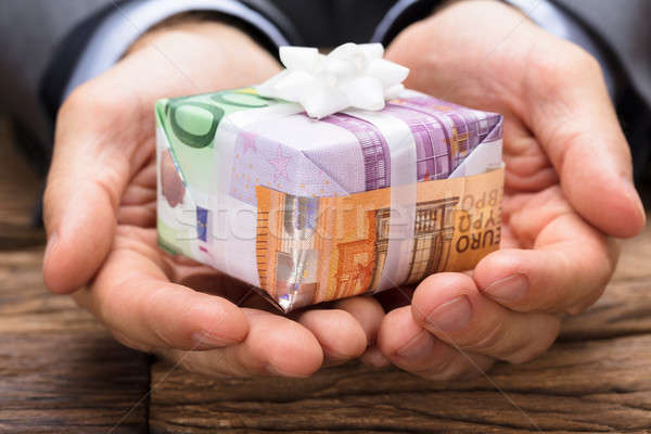 Businessman Holding Gift Box Made From Euro Papernotes Stock photo © AndreyPopov