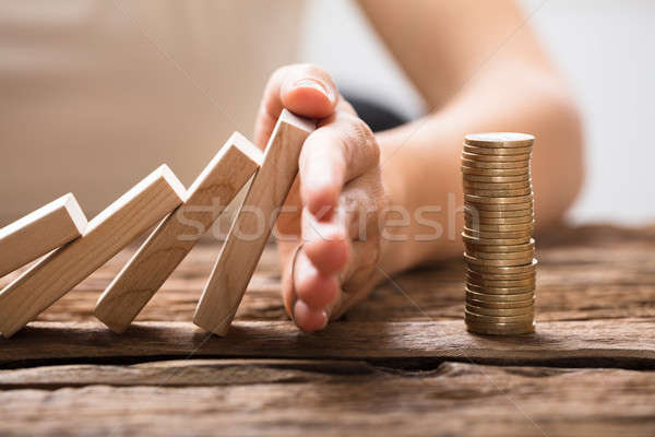 Close-up Of A Businesswoman's Hand Stopping Falling Blocks Stock photo © AndreyPopov