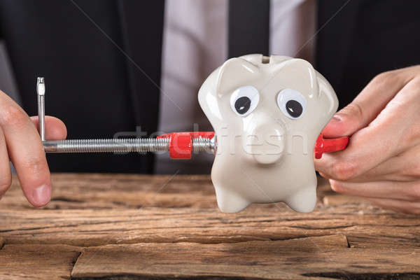 Businessperson Squeezing Piggy Bank In Clamp Tool At Desk Stock photo © AndreyPopov