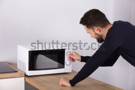 Man Preparing Food In Microwave Oven Stock photo © AndreyPopov