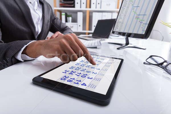 Stock photo: Businessperson Using Calendar On Digital Tablet