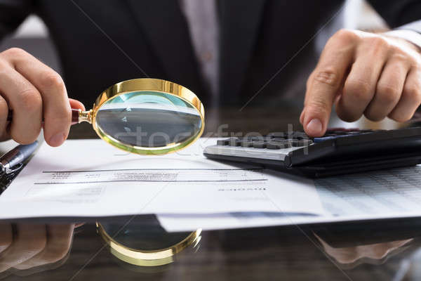Businessperson Calculating Bill With Magnifying Glass Stock photo © AndreyPopov