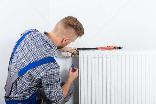 Male Plumber Fixing Thermostat Stock photo © AndreyPopov