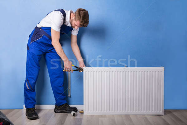 Plumber Installing Radiator With Wrench Stock photo © AndreyPopov