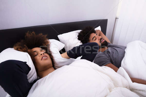 Woman Covering Her Ears While Man Snoring In Bed Stock photo © AndreyPopov