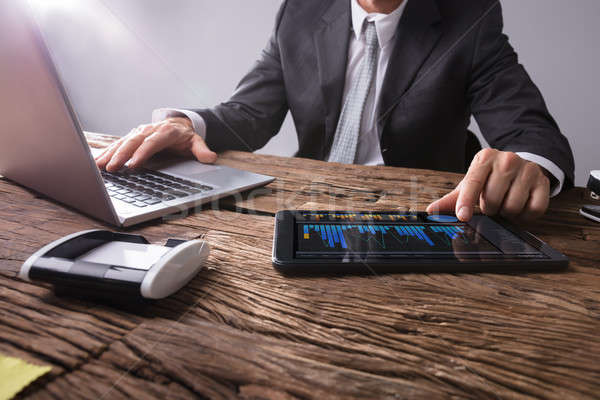 Businessman Analyzing Graph On Digital Tablet Stock photo © AndreyPopov