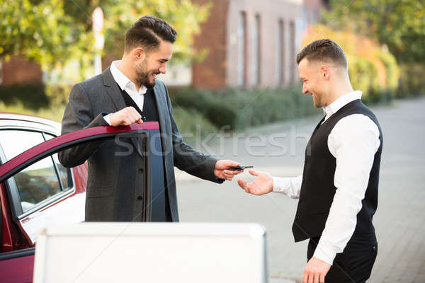 Young Businessman Giving Car Key To Valet Stock photo © AndreyPopov