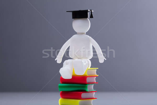 Human Figure Sitting On Stacked Books Stock photo © AndreyPopov