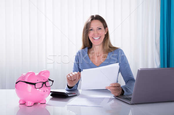 Happy Businesswoman Calculating Invoice Using Calculator Stock photo © AndreyPopov