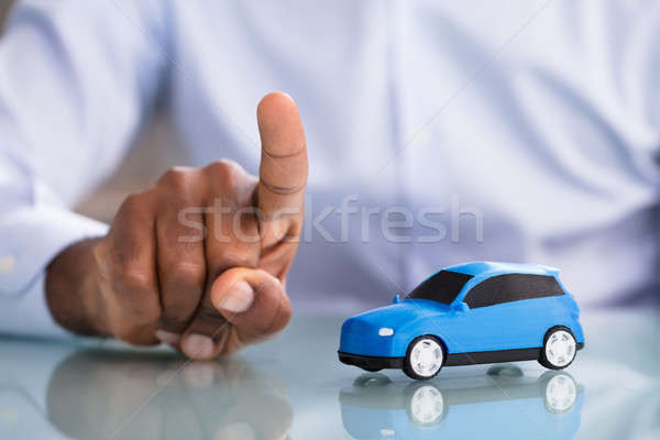 Businessman Pointing Finger With Toy Car On The Desk Stock photo © AndreyPopov