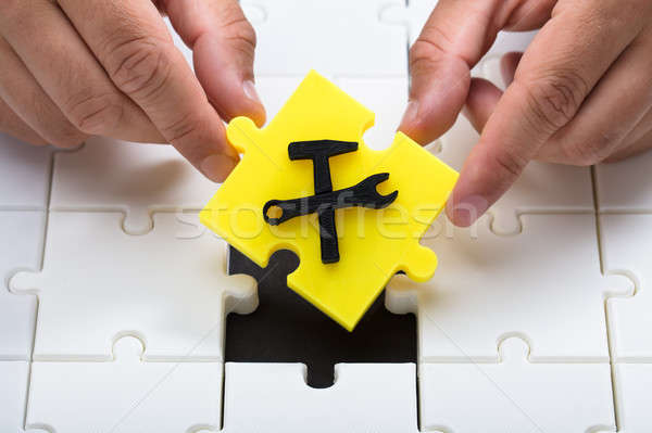 Human hand placing last yellow piece into jigsaw puzzles Stock photo © AndreyPopov
