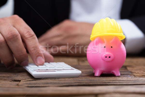 Emberi kéz számológép vmi mellett persely munkavédelmi sisak citromsárga Stock fotó © AndreyPopov