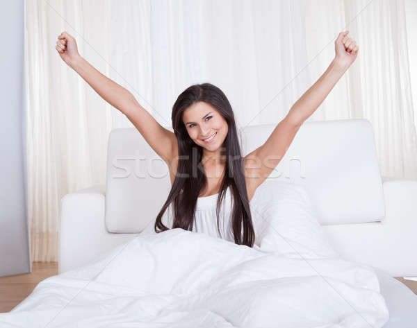 Refreshed young woman rejoicing in bed Stock photo © AndreyPopov