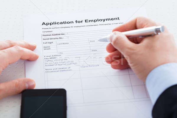 Close-up Of Hand Holding Pen Over Employment Application Stock photo © AndreyPopov