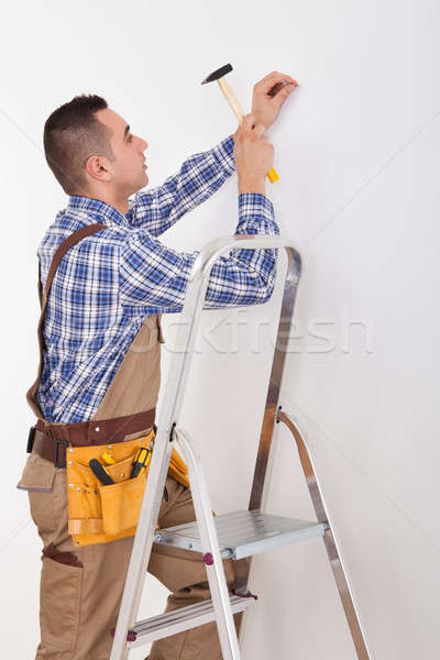 Repairman Hammering Wall With Nail Stock photo © AndreyPopov