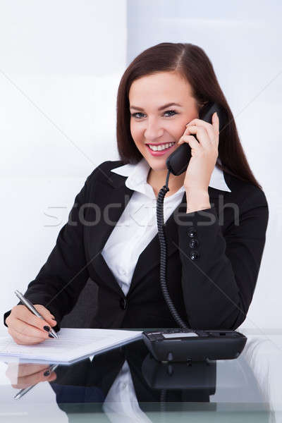 Stock photo: Businesswoman Using Telephone At Desk