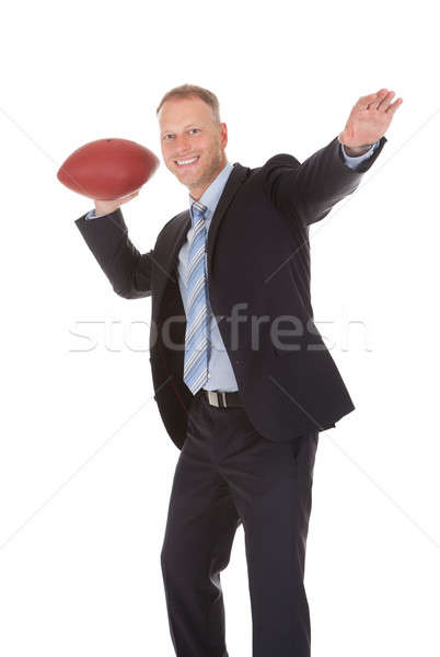 Confident Businessman Throwing Rugby Ball Stock photo © AndreyPopov