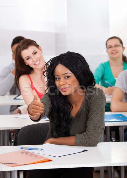 Confident Student Gesturing Thumbs Up In Classroom Stock photo © AndreyPopov