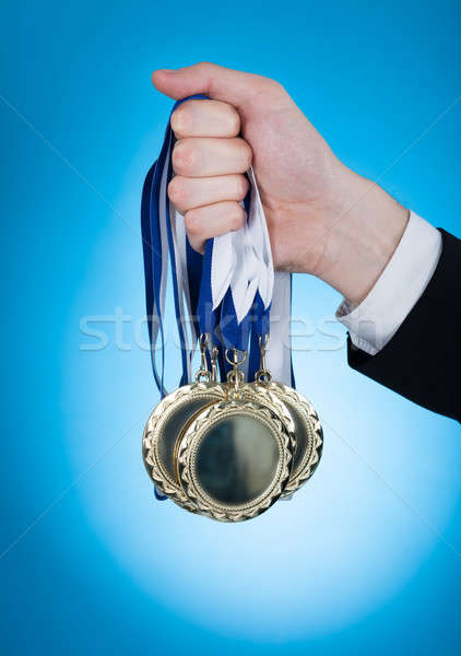 Businessman Holding Medals Stock photo © AndreyPopov
