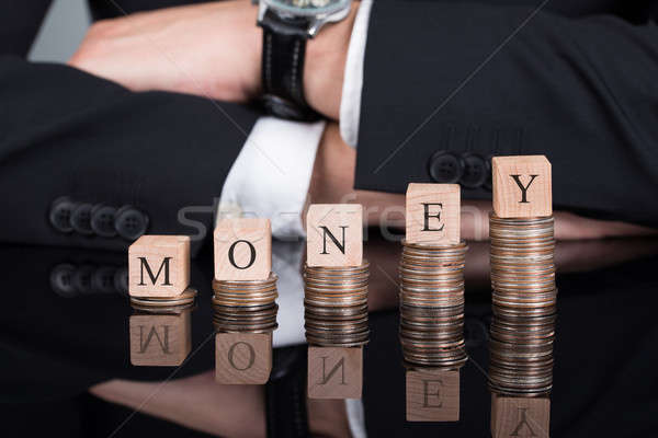 Businessman With Money Blocks On Stacked Coins Stock photo © AndreyPopov