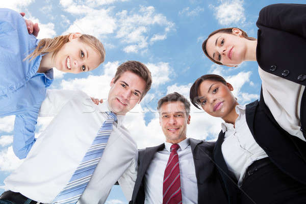Multiethnic Business People Forming Huddle Against Sky Stock photo © AndreyPopov