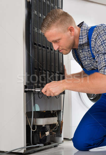 Worker Repairing Refrigerator In House Stock photo © AndreyPopov