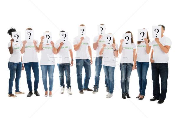 Voluntários faces ponto de interrogação sinais branco Foto stock © AndreyPopov