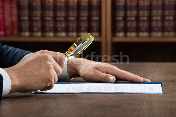 Lawyer Examining Documents With Magnifying Glass Stock photo © AndreyPopov