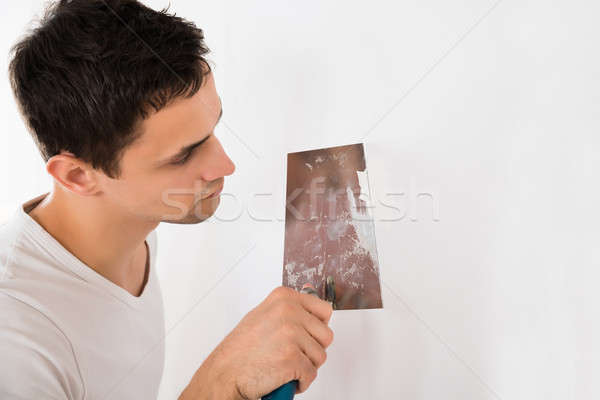 Man Using Putty Knife On White Wall Stock photo © AndreyPopov