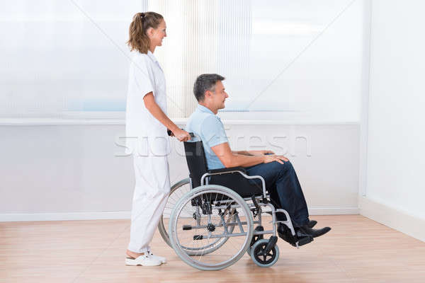 Doctor Pushing Disabled Patient On The Wheelchair Stock photo © AndreyPopov