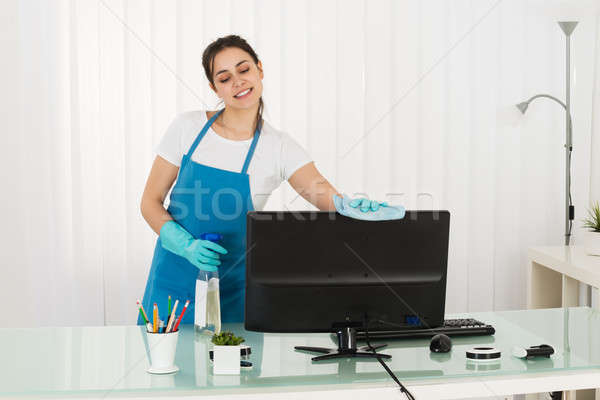 Female Janitor Cleaning Computer With Rag Stock photo © AndreyPopov