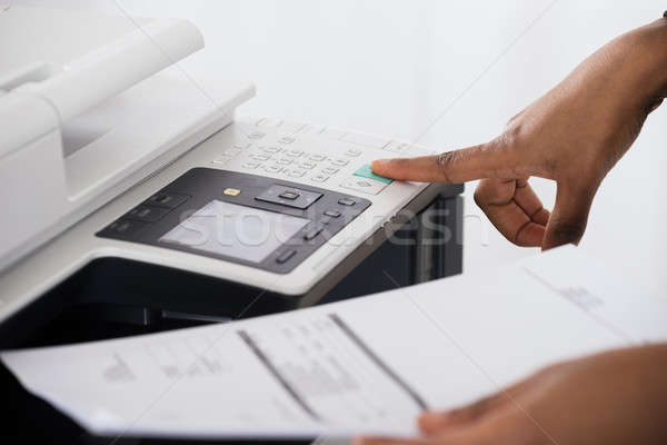 Businesswoman Operating Printer In Office Stock photo © AndreyPopov