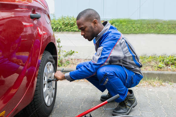 Mechanic Changing Tire With Wrench Stock photo © AndreyPopov