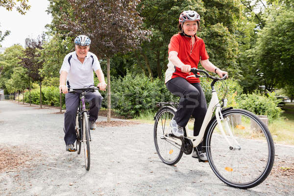 Smiling Senior Couple Cycling In Park Stock photo © AndreyPopov
