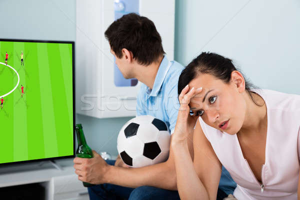Sad Woman Sitting Beside A Man Busy Watching Football Stock photo © AndreyPopov