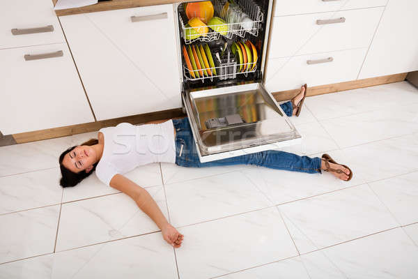 Woman Lying On Floor Under A Dishwasher Stock photo © AndreyPopov