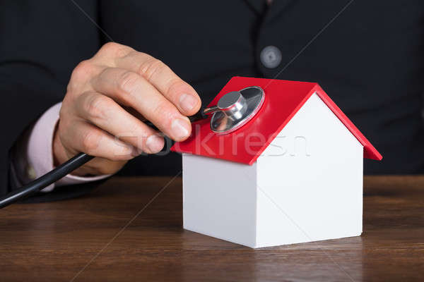 Person Holding Stethoscope On House Model Stock photo © AndreyPopov