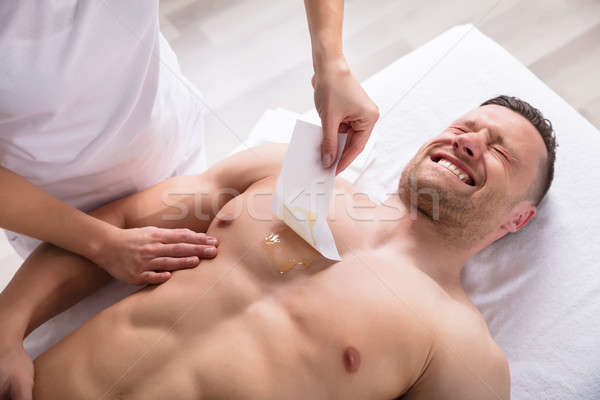 Person Waxing Man's Chest With Wax Strip Stock photo © AndreyPopov