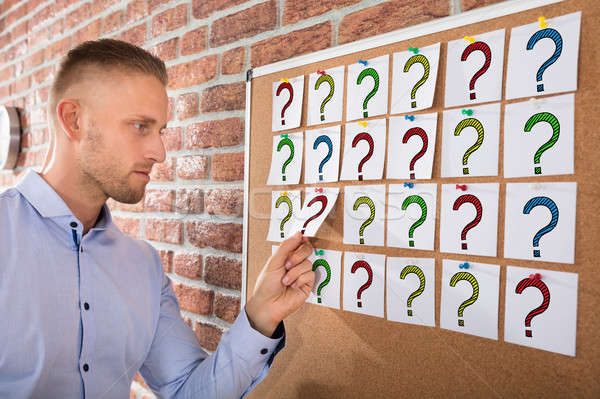 Stock photo: Businessman Looking At Question Marks On Notes