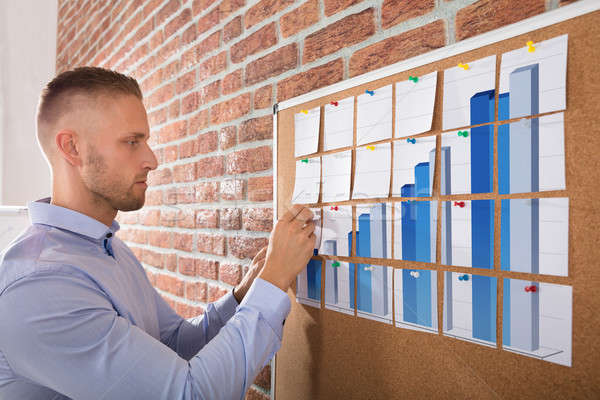 Businessman Arranging Graph Notes On Corkboard Stock photo © AndreyPopov