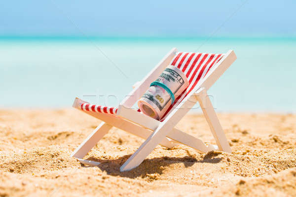 Rolled Up Bundle Of Fifty Dollar Banknotes On Deck Chair Stock photo © AndreyPopov
