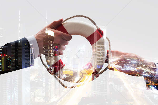 Businessman's Hand Giving Ring Buoy Over City Background Stock photo © AndreyPopov