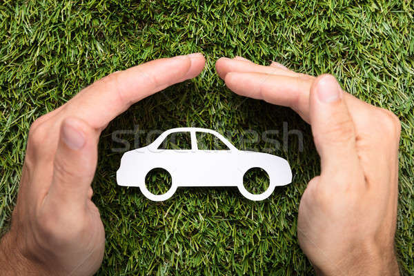 Businessman's Hands Covering Paper Car On Grass Stock photo © AndreyPopov