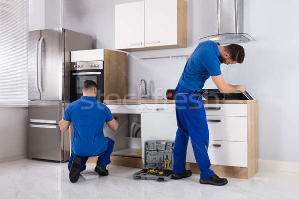 Two Men Checking Induction Stove And Sink Pipe Stock photo © AndreyPopov