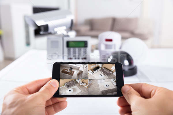 Person Holding Mobile Phone With CCTV Camera Footage On Screen Stock photo © AndreyPopov